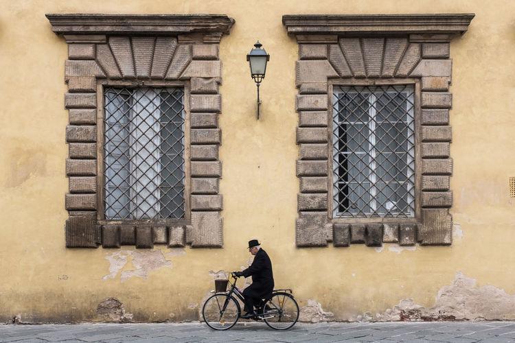 Man sitting on street against building