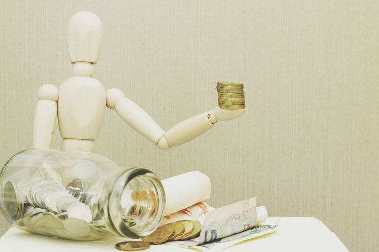 Financial concept Dummy Wooden Doll Money Coins Glass Jar Concept Conceptual Finance Financial Close-up