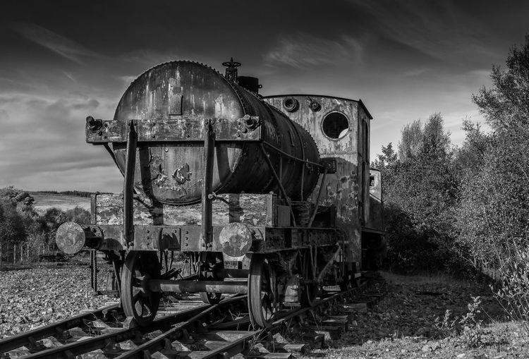 Abandoned Railroad Car On Field Against Sky