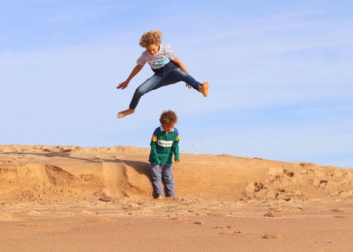 Full length of a boy jumping against sky