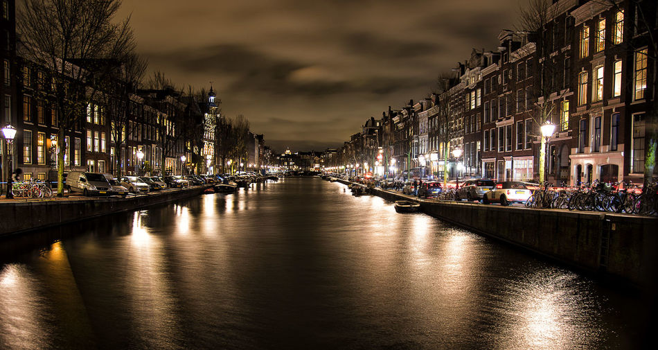 Illuminated canal amidst buildings in city at night