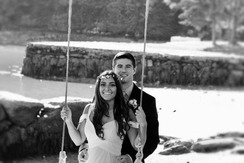 Portrait of groom standing behind bride on swing at park