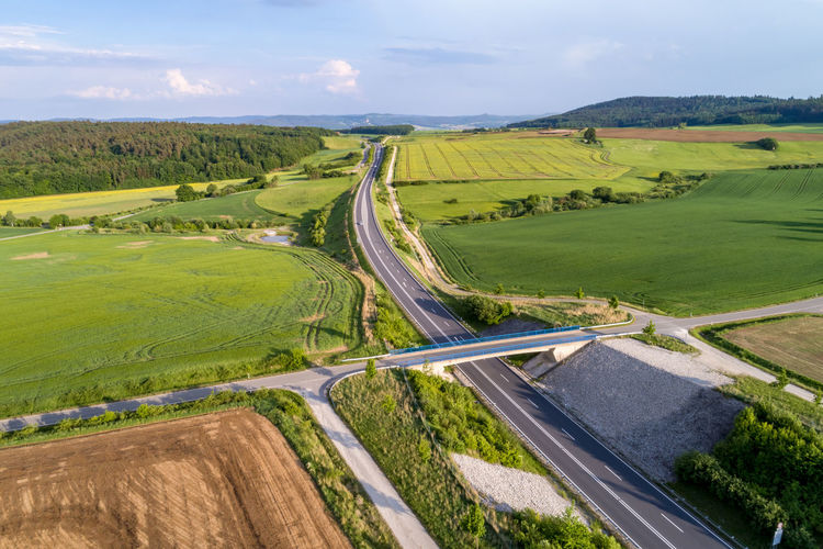 Stretch of the autobahn and rural lansdscape near Coburg in Germany Coburger Land, Air, Autobahn, Birds Eye Perspective, Cargo, Coburg, Europe, European, Fields, Germany, Highway, Landscape, Motorway, Nature, Outdoors, Rural, Sky, Stretch, Summer, Sunlight, Transportation, Travel, Way Landscape Environment Transportation Sky Scenics - Nature Road Tranquil Scene Cloud - Sky Land Beauty In Nature Nature Field Day Plant No People Tranquility Green Color Outdoors