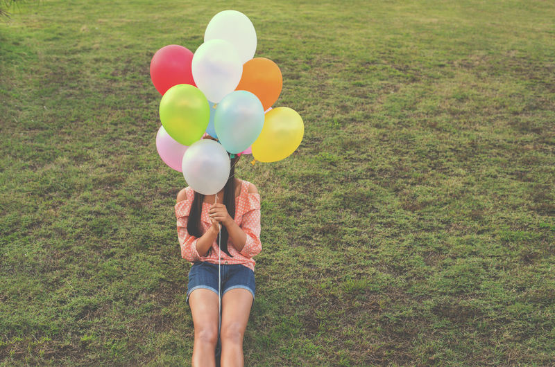 Vintage photo of Happy young girl holding colorful balloons and sitting on grass field, instagram filter Young Women Girl Vintage Balloon Happiness Cheerful Grassland Celebration Decoration Festival Holiday Birthday Happy Multi Colored Colorful Sunset