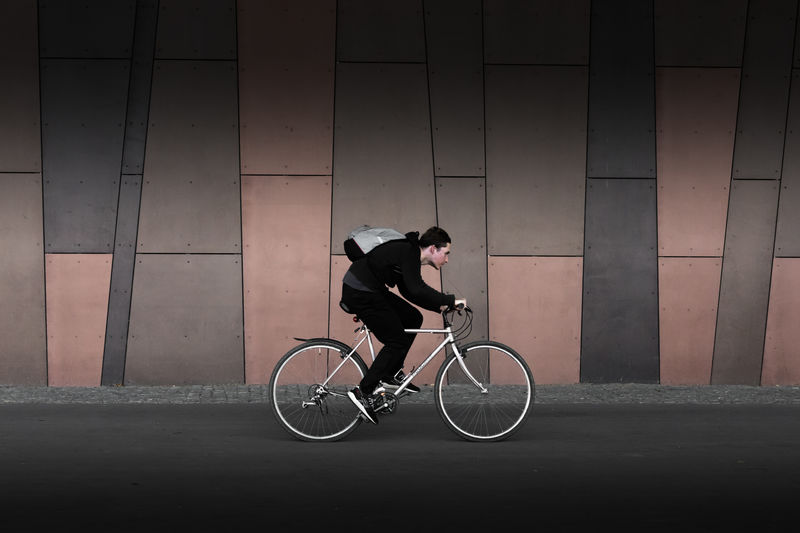 Man riding bicycle on street against wall