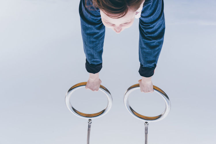 Upside down image of child holding gymnastic rings against gray background
