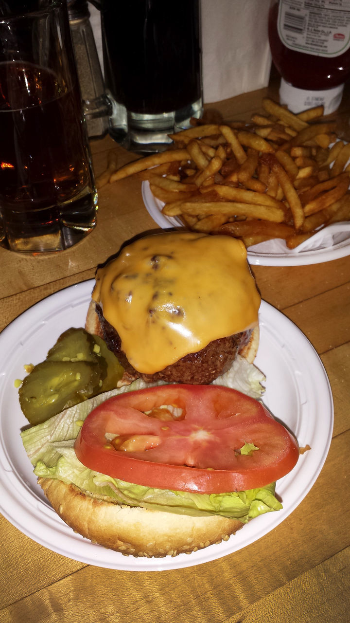 Close-Up Of Burger By Fries And Drink On Table