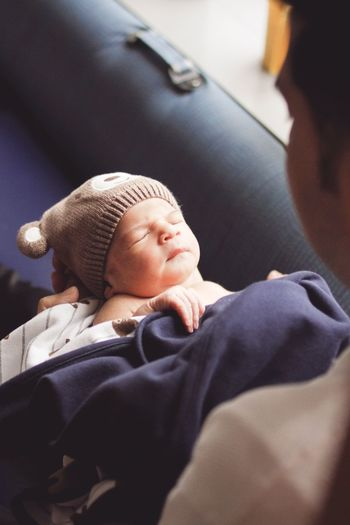 High angle view of father with sleeping baby boy at home