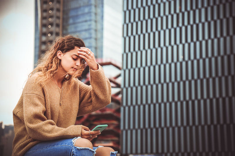 Woman using mobile phone while sitting by building