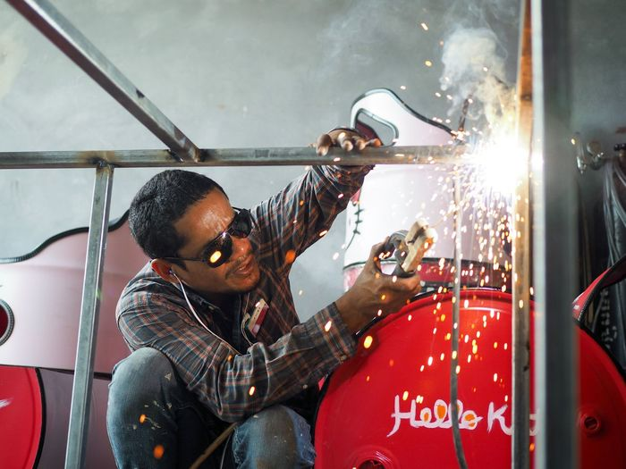 Low angle view of male welder welding metal in factory