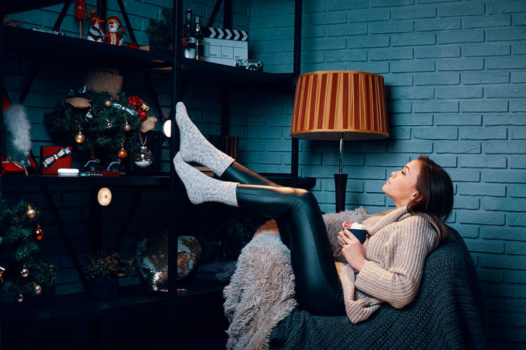 Side view of woman relaxing in sofa at home