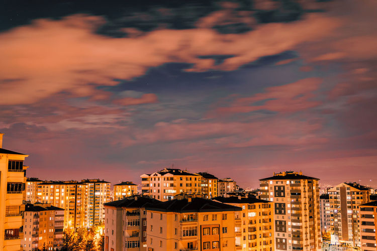 High angle view of illuminated buildings against sky at sunset
