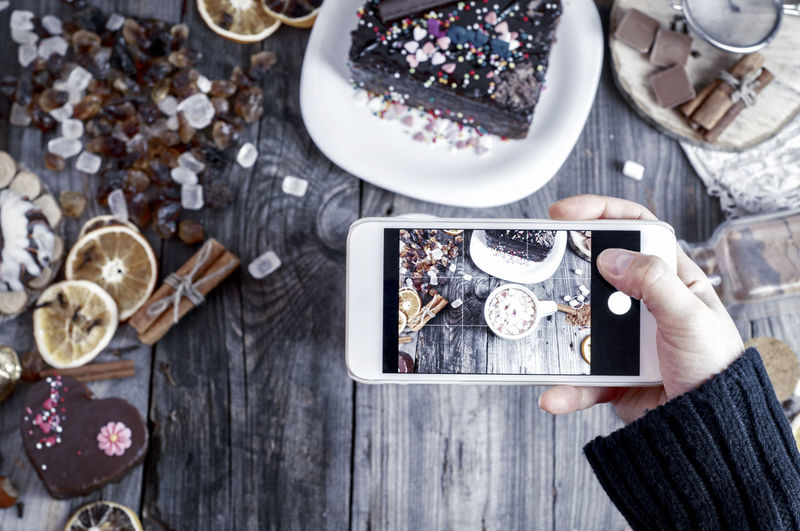 High angle view of hand photographing cake and ingredients on table
