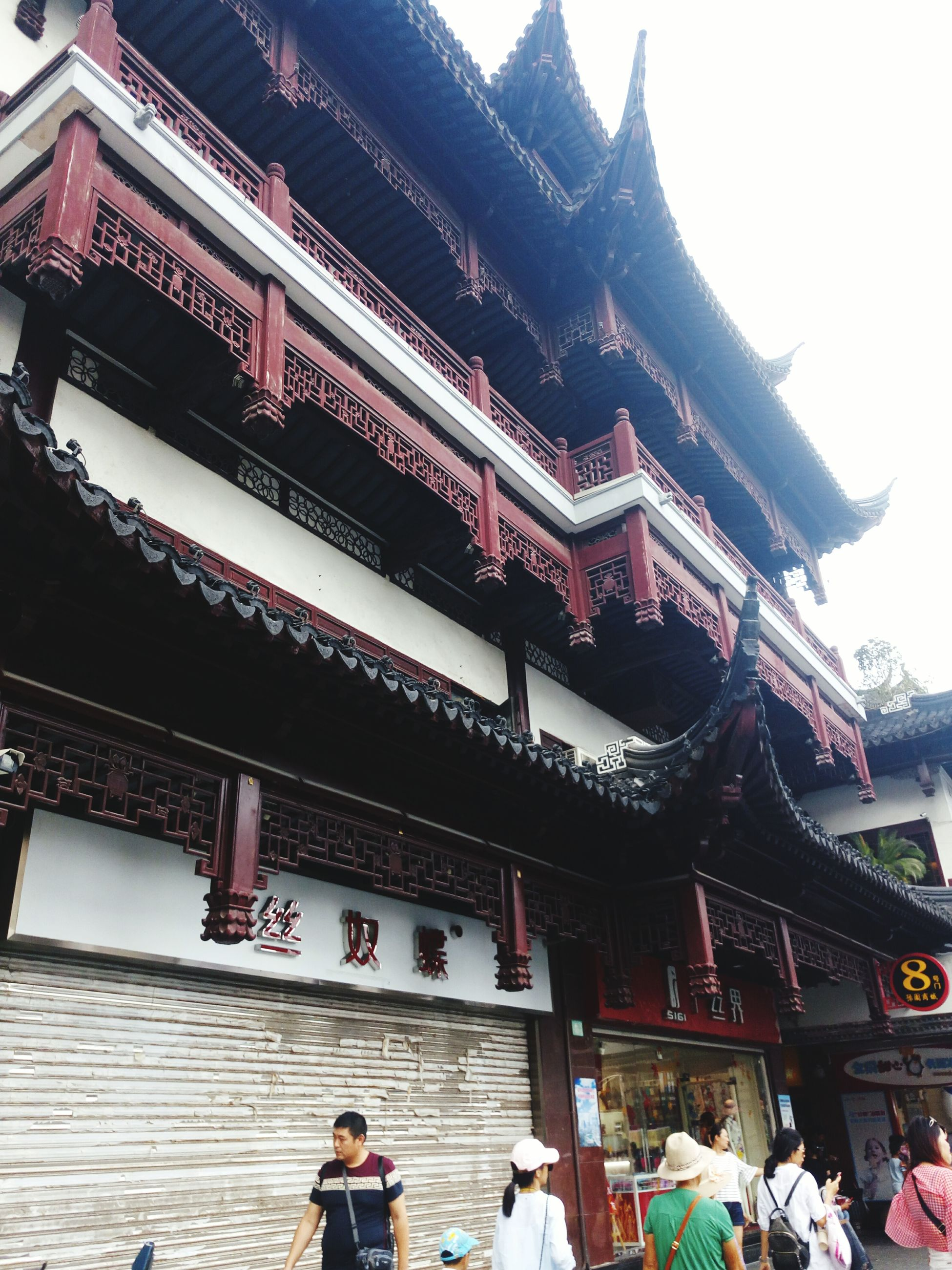 building exterior, architecture, built structure, spirituality, religion, place of worship, lifestyles, temple - building, low angle view, leisure activity, pagoda, culture, famous place, city, outdoors, tourism, person, architectural feature, day, sky, in front of, facade