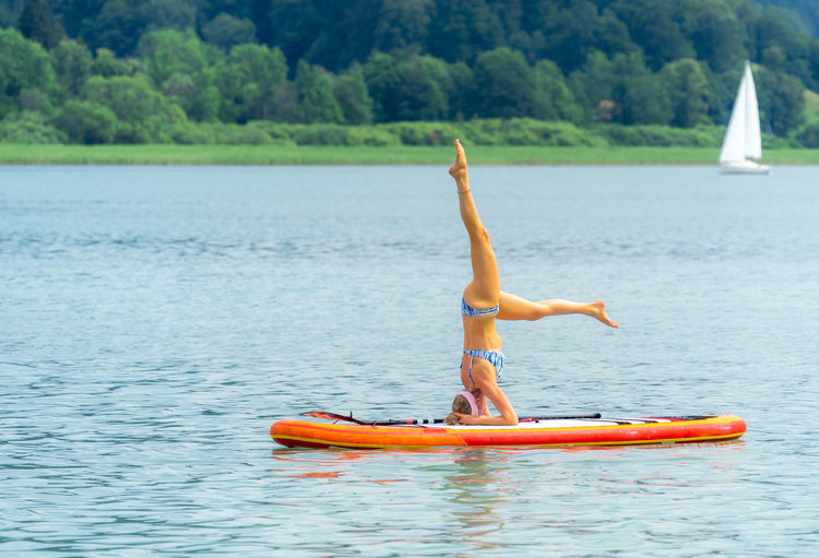 Woman doing headstand on paddleboard in sea
