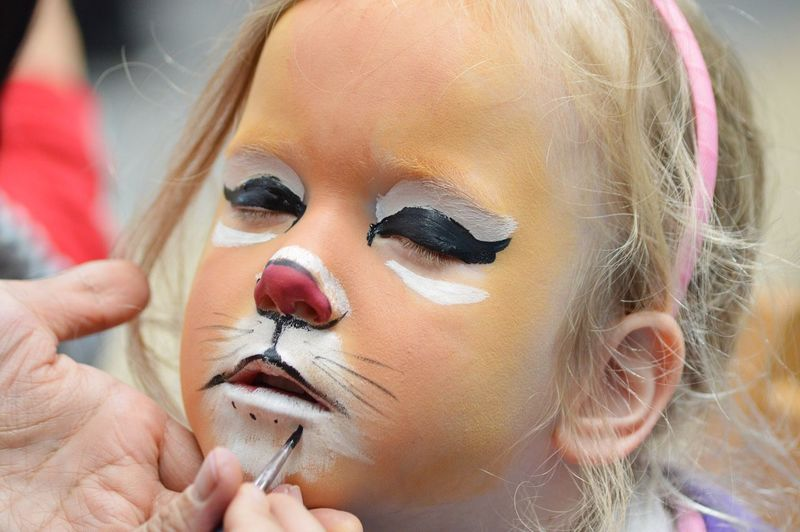 Close-up of girl having face painted like a tiger
