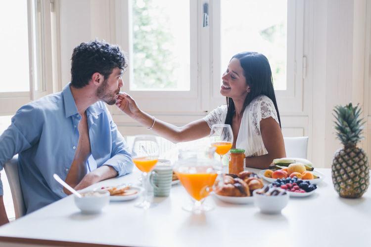 Smiling woman feeding breakfast to boyfriend at home
