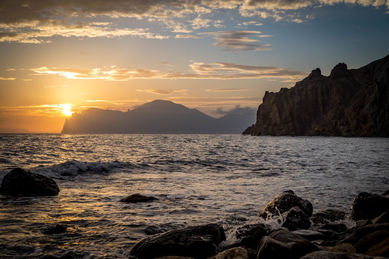 Scenic View Of Sea And Mountains At Sunset