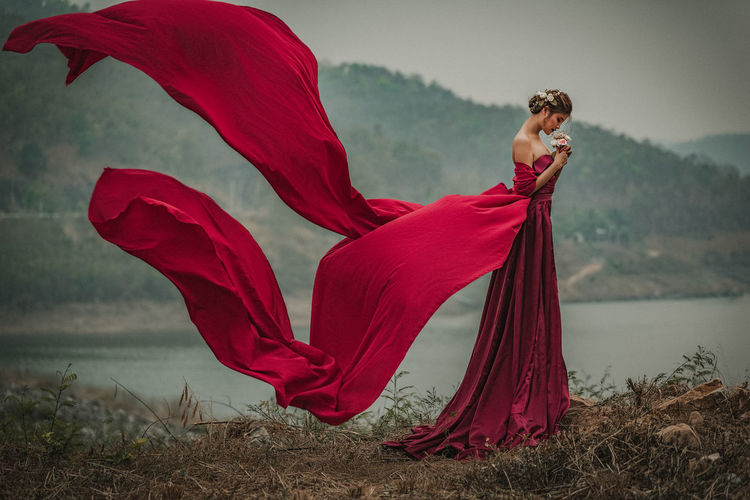 Side View Of Woman Wearing Red Gown By Lake