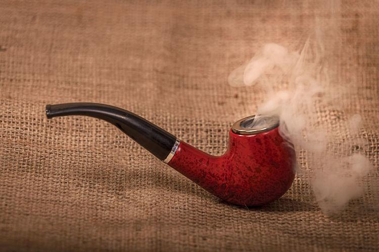 Close up of smoking pipe on burlap