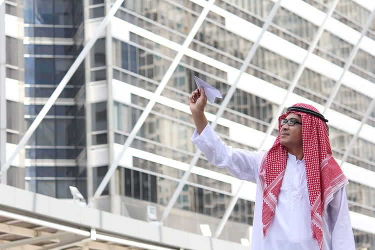 Man wearing dish dash holding paper airplane outside building in city