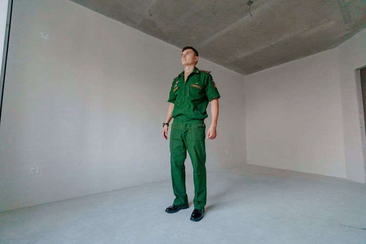 Full length of soldier standing against wall