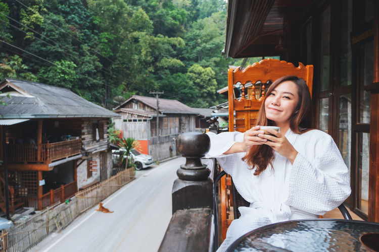 Portrait of smiling woman drinking coffee at balcony