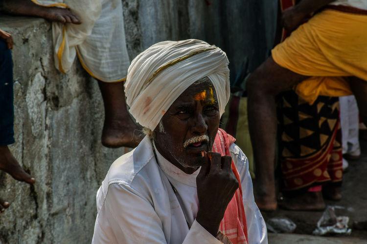 Senior man in turban sitting outdoors at market