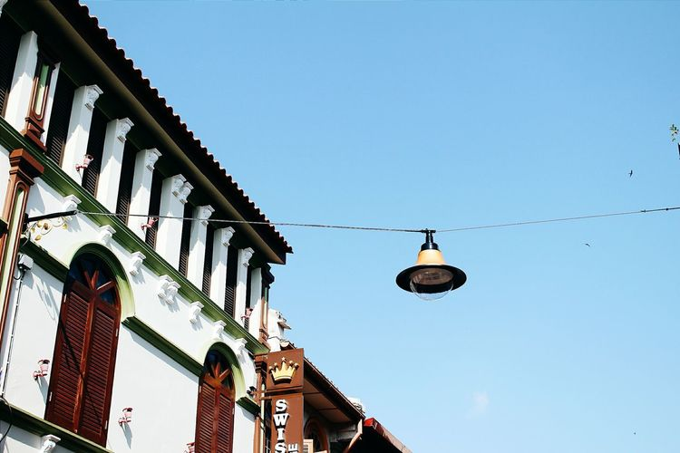 Low angle view of street lamp hanging against clear sky