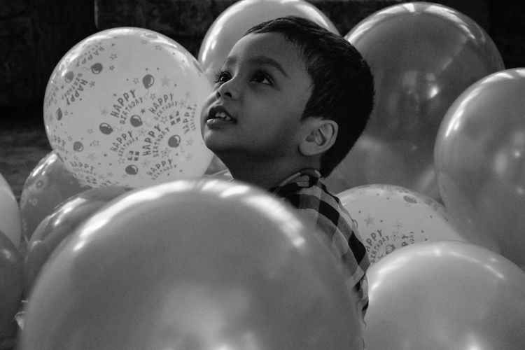 Close-up of cute boy sitting amidst balloons