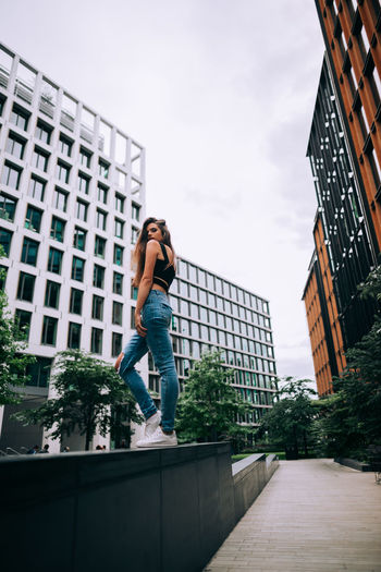 Architecture Building Building Exterior Built Structure Casual Clothing City Full Length Jumping Leisure Activity Lifestyles Low Angle View Modern Nature One Person Outdoors Positive Emotion Real People Sky Vitality Young Adult Young Women