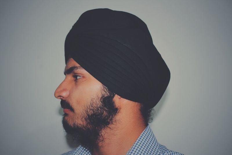 Profile view of young man wearing turban by white wall