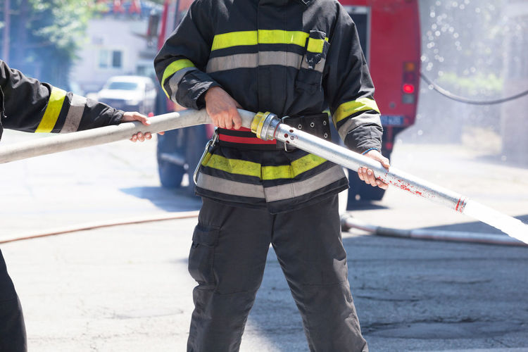 Midsection of firefighters holding fire hose