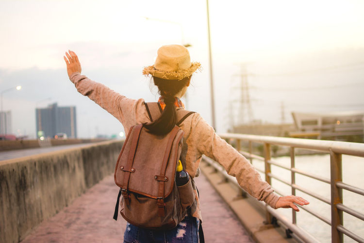 Rear view of woman with arms outstretched standing on bridge against sky