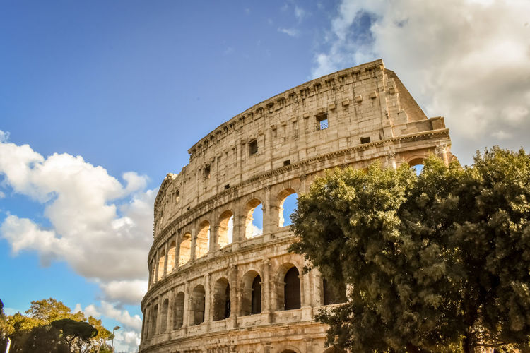 Low angle view of historical building against cloudy sky colloseum