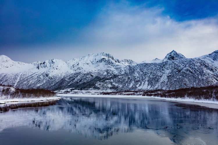 Scenic view of snowcapped mountains by lake against sky during winter