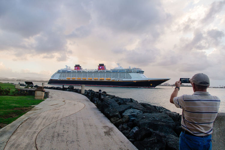 Rear View Of Man Photographing Cruise Ship Sailing In River