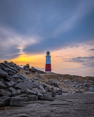 Lighthouse on building by sea against sky during sunset
