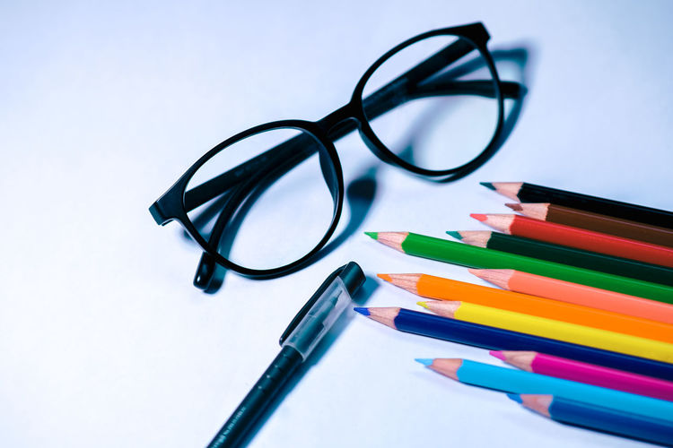 High angle view of eyeglasses on table against white background