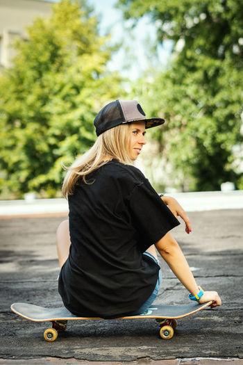Rear view of woman sitting on skateboard