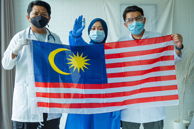 Doctors holding malaysian flag against wall