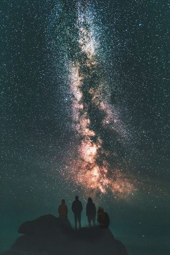 Low angle view of silhouette friends on mountain against star field