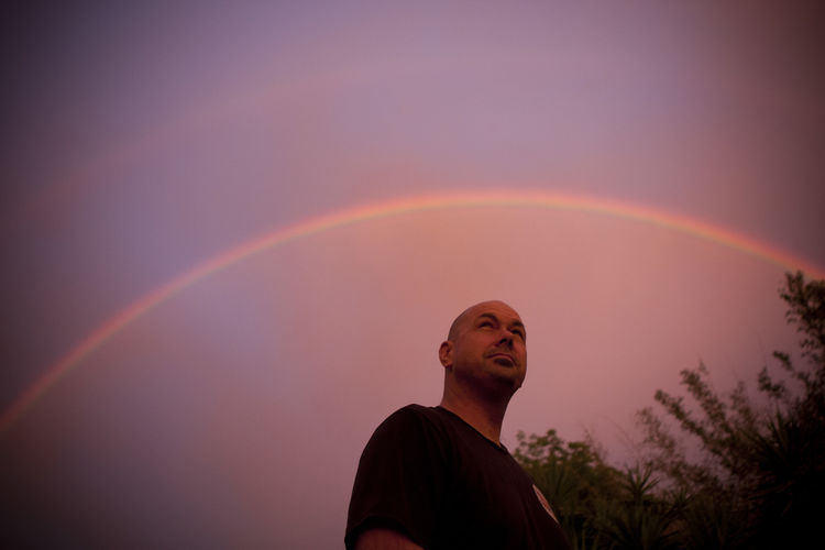 Low angle view of man standing on rainbow against sky