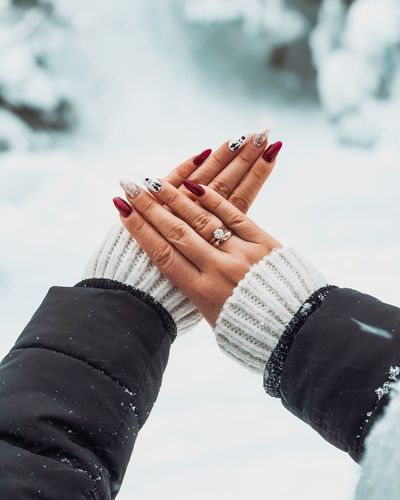 Cropped hands of woman showing painted fingernails during winter