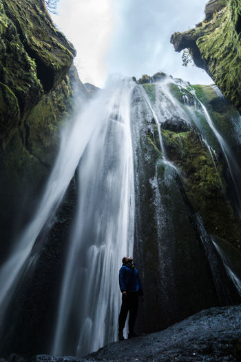 Low Angle View Of Hiker Standing Against Waterfall