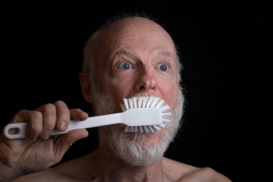 man brushing teeth with very big brush Brushing Adult Adults Only Big Brushes Black Background Brush Close-up Dental Health Dish Brush Holding Human Body Part Human Hand Hygiene Indoors  Large Brush Mature Adult One Person Only Men People Portrait Senior Adult Studio Shot Teeth Washing Up Brush This Is Aging
