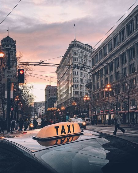 Taxi on street in city during sunset