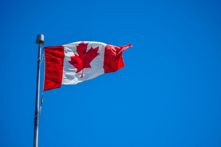 Low angle view of canadian flag waving against blue sky