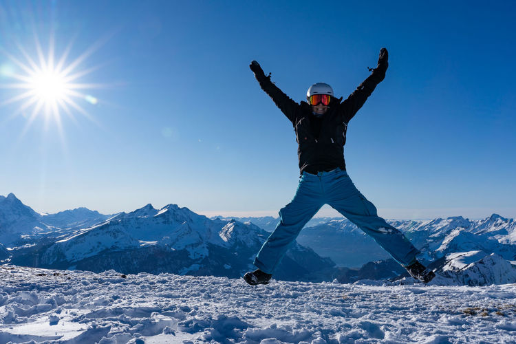 Girl with arms raised on snowcapped mountain against sky
