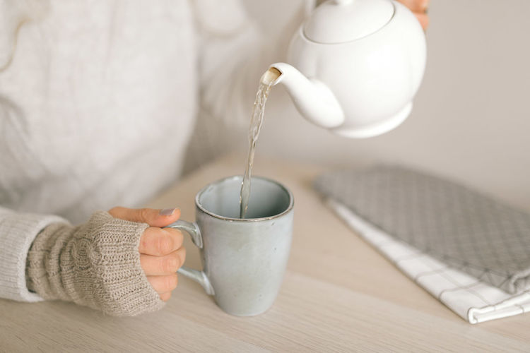 Close-up of hand pouring tea cup
